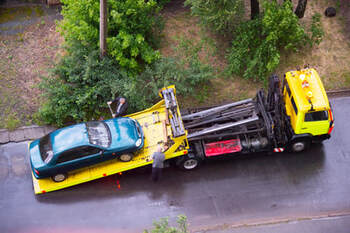 Yellow flat bed tow truck towing away a green car.